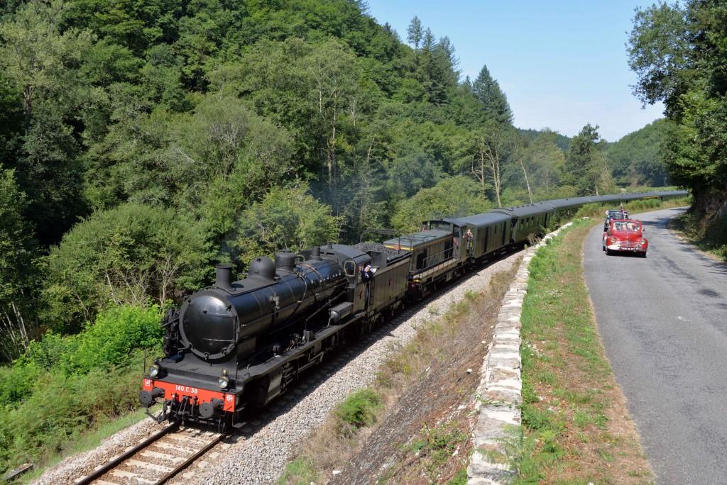 Le train à vapeur roule en parallèle d'une manifestation d'anciens véhicules en août 2015 entre St Léonard de Noblat et Châteauneuf-Bujaleuf. Photo : CFTLP